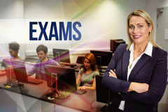 Exams against computer teacher smiling at camera with arms crossed Stock Photography