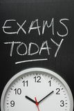 Exams Today and Wall Clock. Exams Today written in white chalk on a blackboard above a wall clock Royalty Free Stock Photos
