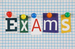 Exams. The word Exams in cut out magazine letters pinned to a background of blue graph paper Royalty Free Stock Photography