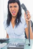 Exasperated businesswoman hanging up the phone. In office royalty free stock photos
