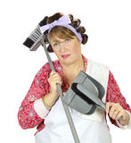 Exasperated Housewife. Middle aged frumpy house looks forlorn and exasperated holding a dust pan and broom stock photography