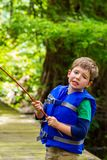Exasperated Little Boy Looks at the Camera in Frustration Because His Fishing Pole is Caught in a Tree. An exasperated little boy looks at the camera in royalty free stock photography