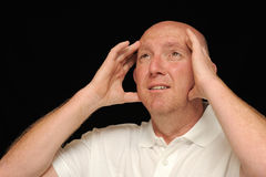 Exasperated man. Head shot of a man holding his hands to his head isolated on a black background, caucasian/white royalty free stock photo