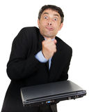 Exasperated man making a fist. Over his closed laptop computer which he is holding i his hand while grimacing at the camera, isolated on white royalty free stock images