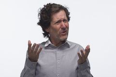 Exasperated man making hand gestures, horizontal. Exasperated man using hand gestures against white background, horizontal royalty free stock photography