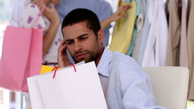 Exasperated man waiting for his girlfriend. While she is doing shopping stock footage
