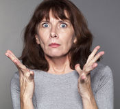 Exasperated mature woman with tense eyes wide open. Portrait of irritated 50's woman with both hands opened with tension for exasperation and frustration Royalty Free Stock Photos