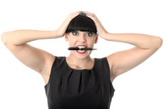 Exasperated Stressed Annoyed Woman With Pen In Mouth. Exasperated stressed annoyed Woman with black hair and hispanic or european features, looking at camera Stock Images