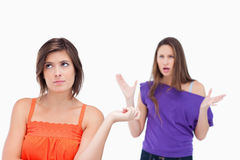 Exasperated teenager standing upright. Teenager standing upright while her friend is shouting at her Royalty Free Stock Image