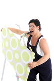 Exasperated woman hanging wallpaper Royalty Free Stock Photos