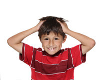 Exasperated Young Boy. Exasperated or frustrated young boy with hands grabbing his hair wearing red shirt on white background royalty free stock image