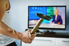 Exasperated the young man the bad news breaks the TV. With a hammer. A psychopath beats TV. Disgruntled viewer. furious, enraged, frenzied, mad, infuriated man Royalty Free Stock Images