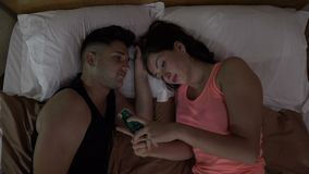 Exasperated young man in love taking away his girlfriend smartphone kissing and hugging her in bed. Exasperated young man in love taking away his girlfriend stock footage