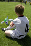 Exausted boy takes a rest. In the halftime of a football match royalty free stock image