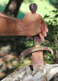 Excalibur sword in the stone. And the hand of king arthur Royalty Free Stock Photo