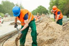 Excavación de los trabajadores de construcción Imágenes de archivo libres de regalías