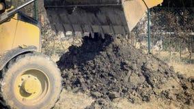 Excavación del agujero El cavador amarillo funciona en el edificio Maquinaria de construcción, trabajos de la tierra almacen de video
