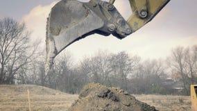 Excavación del agujero El cavador amarillo funciona en el edificio Maquinaria de construcción, trabajos de la tierra metrajes