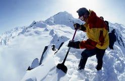 Excavación en nieve en un top de la montaña en Alaska Imágenes de archivo libres de regalías