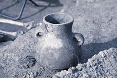 Excavaciones arqueológicas El artefacto encontrado, envejeció el tarro de cerámica dañado en la tierra, restos humanos en un fond foto de archivo