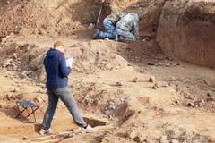 Excavaciones arqueológicas Los arqueólogos en un proceso picador, investigando la tumba con los huesos humanos, dibujando el rema foto de archivo libre de regalías