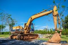 Excavador amarillo contra emplazamiento de la obra Imagen de archivo libre de regalías
