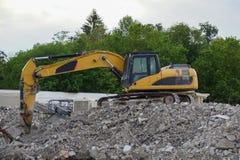 Excavador amarillo en el sitio de demolición Fotos de archivo libres de regalías