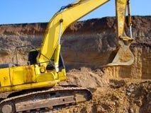 Excavador amarillo en emplazamiento de la obra imagen de archivo libre de regalías