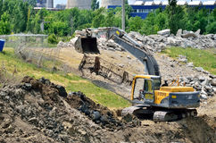Excavador amarillo en un emplazamiento de la obra Imagen de archivo