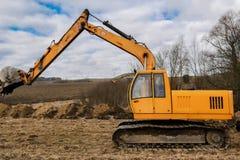Excavador amarillo que cava la tierra fotografía de archivo