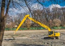 Excavador amarillo que hace servicios de la limpieza y de mantenimiento del lago Imagenes de archivo