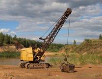 Excavador amarillo viejo. Imagen de archivo