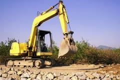 Excavador anaranjado en el emplazamiento de la obra Foto de archivo