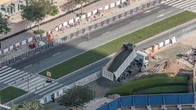 Excavador, camión y graduador trabajando en el sitio de la construcción de carreteras en el timelapse céntrico de Dubai metrajes