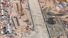 Excavador, camión y graduador trabajando en el sitio de la construcción de carreteras en el timelapse céntrico de Dubai almacen de video
