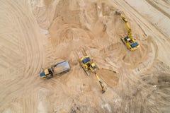 Excavador cargado de la arena en un camión volquete en el emplazamiento de la obra foto de archivo libre de regalías
