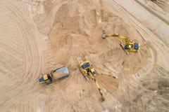 Excavador cargado de la arena en un camión volquete en el emplazamiento de la obra imagenes de archivo