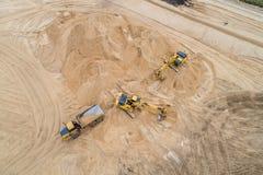 Excavador cargado de la arena en un camión volquete en el emplazamiento de la obra foto de archivo