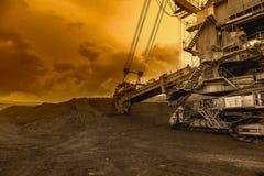 Excavador de rueda de cubo gigante en cielo de la puesta del sol Foto de archivo