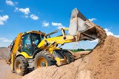 Excavador del cargador de la rueda que descarga la arena Foto de archivo libre de regalías