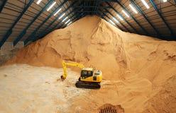 Excavador en un almacenamiento del azúcar crudo Fotos de archivo libres de regalías
