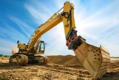 Excavador grande delante del cielo azul Imagenes de archivo