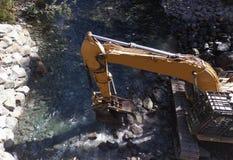 Excavador Moving Rocks en el río imagenes de archivo