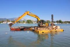 Excavador que draga en la plataforma flotante Fotos de archivo