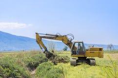 Excavador que se coloca en campo con el aumento del cubo Imagen de archivo