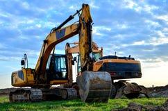 Excavador seguido pesado en un emplazamiento de la obra en un fondo de un edificio residencial y las gr?as de construcci?n en un  foto de archivo