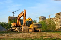 Excavador seguido pesado en un emplazamiento de la obra en un fondo de un edificio residencial y las gr?as de construcci?n en un  imagenes de archivo