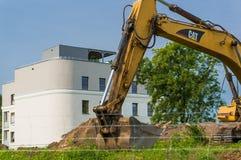 Excavador y bloque de apartamentos Foto de archivo