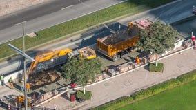 Excavador y camión que trabajan en el sitio de la construcción de carreteras en el timelapse céntrico de Dubai almacen de metraje de vídeo