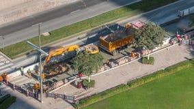 Excavador y camión que trabajan en el sitio de la construcción de carreteras en el timelapse céntrico de Dubai almacen de video